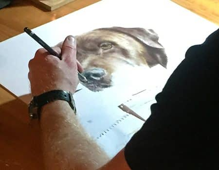 artist doing drawing of brown labrador at drawing table